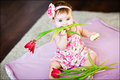 Pretty baby girl with tulips sitting on the carpet