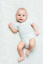 Pretty baby is lying on the carpet white Royalty Free Stock Photo
