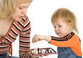 Pretty baby and mother play chess Stock Image