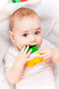 Pretty baby with toys the cute craking multicolored Royalty Free Stock Photos