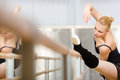 Pretty ballerina stretches herself near barre and mirrors in the classroom Royalty Free Stock Photos