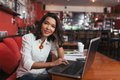 Pretty bar owner smiling working on laptop at the table Stock Photo