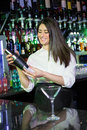 Pretty bartender mixing a cocktail drink in cocktail shaker Royalty Free Stock Photo