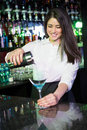 Pretty bartender pouring a blue martini drink in the glass at bar Royalty Free Stock Photos