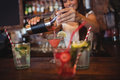 Pretty bartender pouring a cocktail drink in the glass Royalty Free Stock Photo