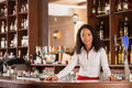 Pretty bartender smiling vietnamese standing behind counter Stock Image