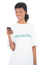 Pretty black haired volunteer texting with her mobile phone on white background Stock Photography