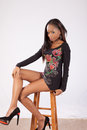 Pretty black woman in flowered blouse sitting on a stool looking at the camera with shirt Stock Photo