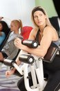 Pretty blond doing workout at the gym young girl on weight machine Royalty Free Stock Image