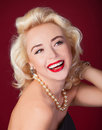 Pretty blond girl model like marilyn monroe on red background Stock Photos