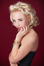 Pretty blond girl model like marilyn monroe on red background Royalty Free Stock Photos