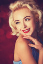Pretty blond girl model like marilyn monroe on red background Royalty Free Stock Photo