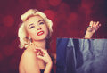 Pretty blond girl model like marilyn monroe with shopping bag on red background Stock Image