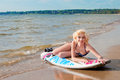 Pretty blond girl model like marilyn monroe with surfing board on a beach Stock Images