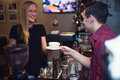 Pretty blond girl taking her order with pleasant smile barista is passing cup pf cofee Royalty Free Stock Images