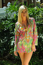 Pretty blond girl wearing beach tunic looking straight to the camera in tropical garden Stock Images