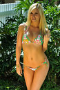 Pretty blond girl wearing bikini looking straight to the camera in tropical garden Royalty Free Stock Photos