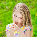 Pretty blond little girl with long hair eating ice adorable cream in summer sunny day on grass green background Royalty Free Stock Photos