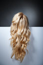 Pretty blond model hiding behind a big sheet of blank paper only her hair shown Royalty Free Stock Photos