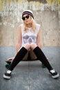Pretty blond skater girl sitting on skateboard Royalty Free Stock Photos