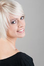 Pretty blond woman with a beautiful smile looking back over her shoulder at the camera close up head and shoulders on grey Royalty Free Stock Images