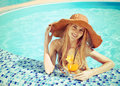 Pretty blond woman hat enjoying cocktail swimming pool Stock Images