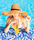 Pretty blond woman hat enjoying cocktail swimming pool Royalty Free Stock Photos