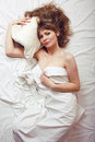 Pretty blond woman laying in bed under white shits Royalty Free Stock Photography