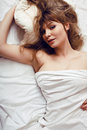 Pretty blond woman laying in bed under white shits Royalty Free Stock Images