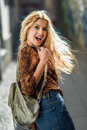 Pretty blond woman, model of fashion, smiling with flying hair