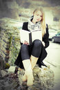 Pretty blond woman reading a book outdoors Royalty Free Stock Photo