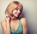 Pretty blond young woman with short hairstyle looking down. Colo