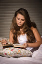 Pretty blonde girl with book lying on the bed Royalty Free Stock Photos