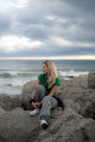 A pretty blonde girl sitting alone young all on the big stones near the sea Royalty Free Stock Photography