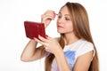 Pretty blonde girl touches up eyelashes on white background Royalty Free Stock Photography