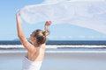 Pretty blonde holding up white shawl on the beach a bright day Royalty Free Stock Photos