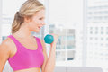 Pretty blonde lifting dumbbells and smiling at home in the living room Royalty Free Stock Images
