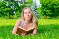 Pretty blonde lying on the grass and holds thick book in hands Stock Photo