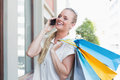 Pretty blonde making a call and holding shopping bags Royalty Free Stock Photo