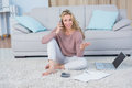 Pretty blonde sitting on carpet phoning at home in the living room Stock Photography