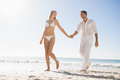 Pretty blonde walking away from man holding her hand men on the beach Stock Image