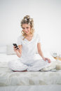 Pretty blonde wearing hair curlers text messaging sitting on cosy bed Royalty Free Stock Images