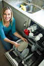 Pretty blonde woman emptying the dishwasher in kitchen Royalty Free Stock Image