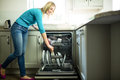 Pretty blonde woman emptying the dishwasher in kitchen Stock Photo