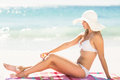 Pretty blonde woman putting sun tan lotion on her leg Royalty Free Stock Photo