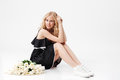 Pretty Blonde woman sitting on floor with bouquet of flowers Royalty Free Stock Photo