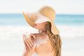Pretty blonde woman spreading sun tan lotion on her shoulder at the beach Royalty Free Stock Photos