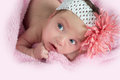 Pretty blue eyed baby wearing a flower headband laying on pink blanket looking up Stock Photo