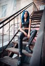 Pretty blue-haired rock girl informal model, dressed in black leather pants and topic, sits on stairway