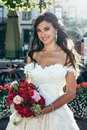 Pretty bride with charming smile hold the wedding bouquet of red and oink flowers. Outdoor portrait. Royalty Free Stock Photo